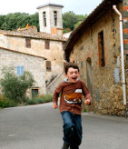 boy-running-down-street-tuscany-with-kids